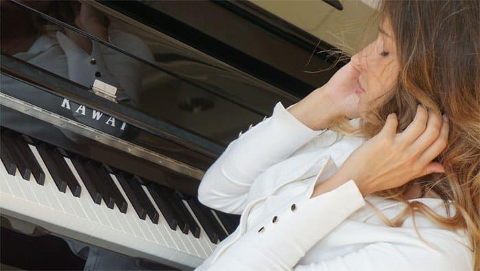 Eine Frau sitzt an der Klaviertastatur und hält sich die Ohren zu.
