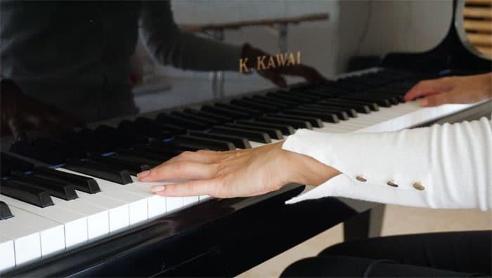 Zwei Frauenhände spielen auf der Klaviertastatur.